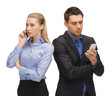 man and woman with cell phones