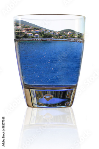 Glass of vacation. Greek island in a glass of water