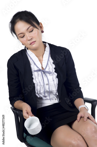 Tired business woman sleeping in her chair and holding empty cof