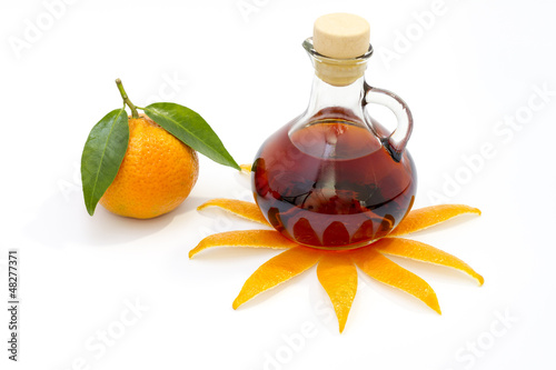 Bottle of liquor with mandarin isolated on white