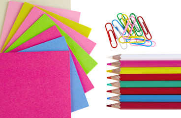 Colorful pencils, clips  and note papers on white background