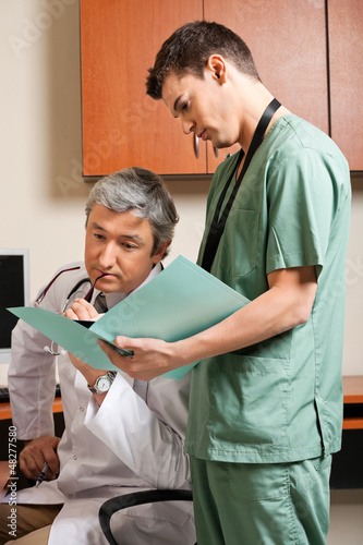 Technician Showing Report To Doctor
