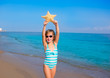 child kid girl in summer beach vacations with starfish