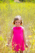 child kid girl in spring yellow flowers field and pink dress