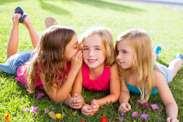 children girls playing whispering on flowers grass
