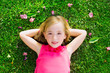 Blond kid girl lying on garden grass smiling aerial view