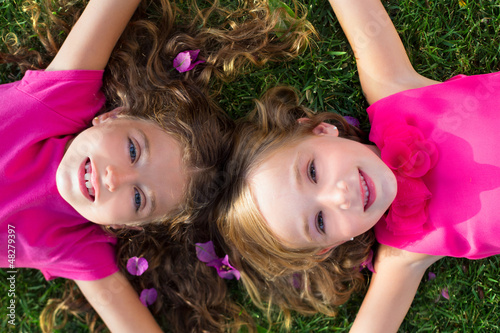 children friend girls lying on garden grass smiling