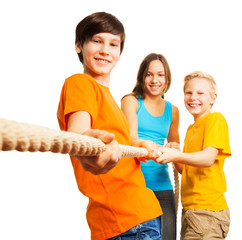 Three happy kids pull the rope