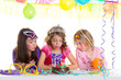 children happy girls blowing birthday party cake