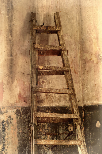 Shabby background with a ladder in the room with the old walls.