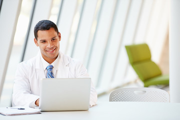 Doctor Using Laptop Sitting At Desk In Modern Hospital