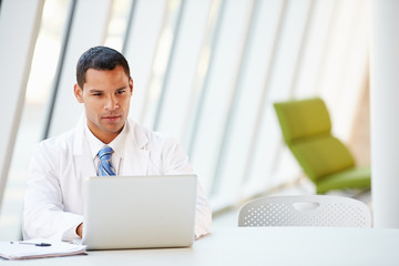 Doctor Using Laptop Sitting At Desk In Modern Hospital