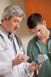 Medical Professionals Looking At Medicine Box