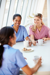 Group Of Nurses Chatting In Modern Hospital Canteen