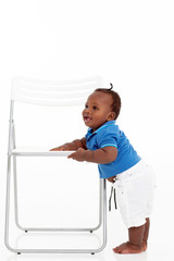 cute african american baby boy learning to walk around a chair