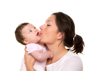 Beautiful mother kissing baby girl hug on white