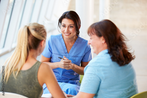 Nurse Meeting With Teenage Girl And Mother In Hospital