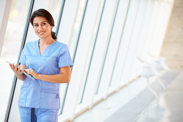 Nurse Using Digital Tablet In Corridor Of Modern Hospital