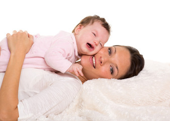 Baby girl crying and mother lying together on white fur