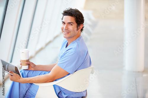 Doctor Using Digital Tablet On Coffee Break In Hospital