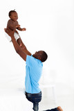 happy african american father and son playing in bedroom