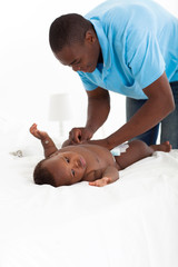 african american father changing baby boy's nappie