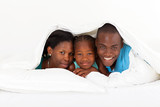 happy african american family lying under duvet on bed