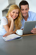 Young couple websurfing with tablet in home kitchen