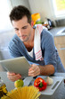Closeup of smiling man in kitchen using tablet