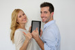 Cheerful couple with tablet showing thumbs up