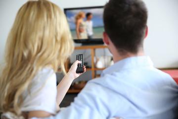 Back view of couple choosing tv program