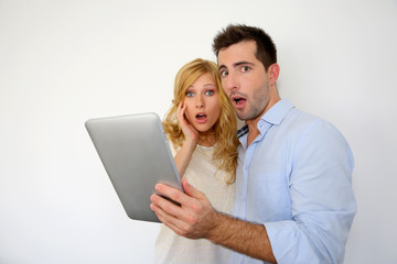 Couple with astonished expression in front of tablet