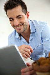 Cheerful young man websurfing on digital tablet at home