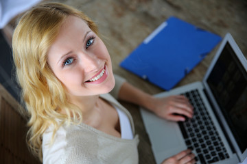 Upper view of blond woman using laptop