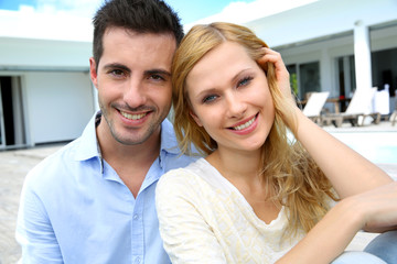 Cheerful young couple sitting in front of modern house