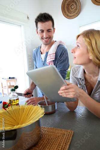 Young people in kitchen preparing pasta dish