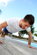 Young man doing pushups on pool deck