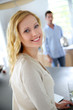 Blond woman standing in kitchen, man in background