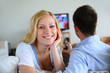 Smiling blond girl watching tv with boyfriend