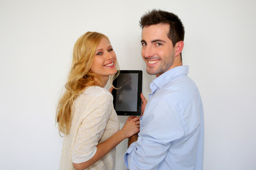 Couple standing on white background with tablet