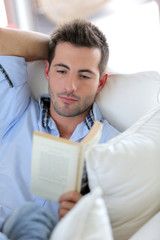 young man reading book in sofa