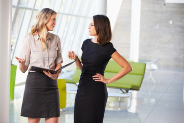 Two Businesswomen Having Informal Meeting In Modern Office