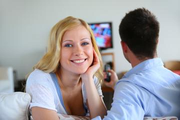 Smiling blond girl watching tv with boyfriend