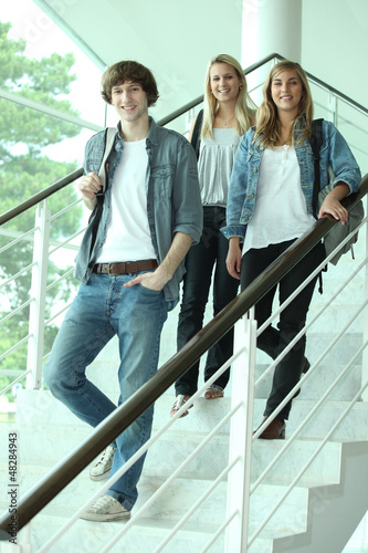 Three teenagers walking down stairs