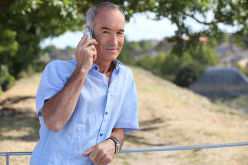 Grey-haired man making telephone call in park