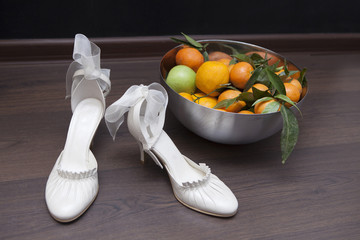 pair of shoes standing on the floor near the dish with mandarins