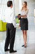 Businessman And Businesswoman Shaking Hands In Office
