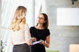 Two Businesswomen Having Informal Meeting In Modern Office