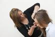 Coiffeuse coiffant une jeune femme