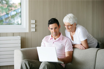 Young man and a senior woman looking at a laptop